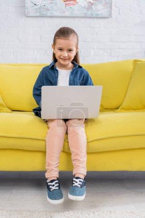 Photo pour Enfant avec ordinateur portable souriant à la caméra sur canapé jaune - image libre de droit