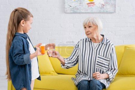 Photo pour Fille prudente tenant des pilules et de l'eau près de grand-mère sur le canapé - image libre de droit