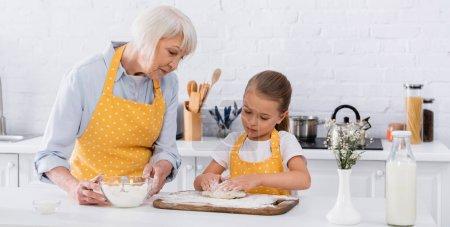 Photo pour Enfant faisant de la pâte près de mamie dans un tablier contenant de la farine, bannière - image libre de droit