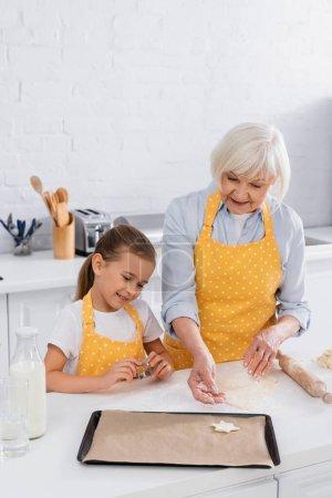Happy kid and grandmother preparing cookie in kitchen