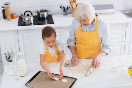 Photo for High angle view of child putting dough on baking sheet near granny with rolling pin - Royalty Free Image