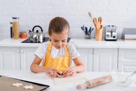 Kind mit Ausstecher steht neben Teig und Nudelholz in Küche