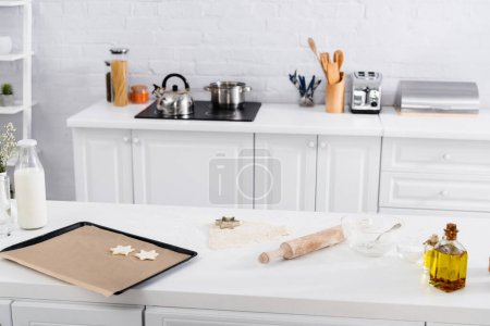 Dough, cookie cutter and rolling pin on table near flour in kitchen