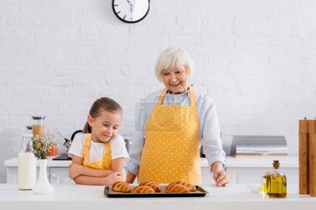 Photo pour Joyeux mamie et enfant regardant des croissants savoureux sur la table de cuisine - image libre de droit