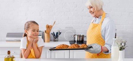 Photo pour Grand-mère tenant des croissants sur une plaque à pâtisserie près d'un enfant souriant, bannière - image libre de droit