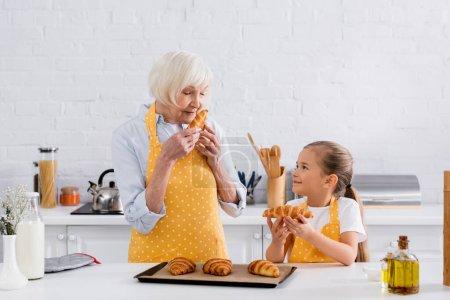 Photo pour Grand-mère senior sentant croissant près de la petite-fille dans la cuisine - image libre de droit