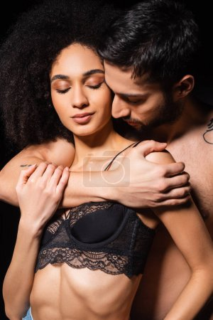 Shirtless man embracing seductive african american woman isolated on black