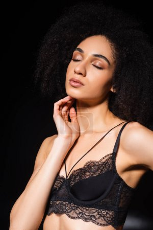 Photo for African american woman in bra posing with closed eyes on black background - Royalty Free Image