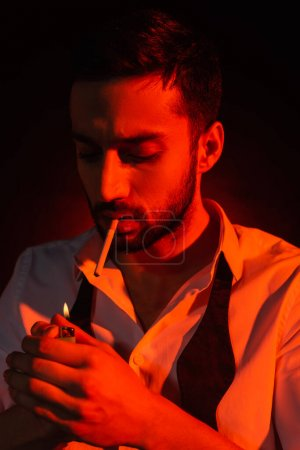Photo for Bearded man with cigarette holding lighter in red light on black background - Royalty Free Image