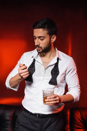 Photo for Bearded man with cigarette and whiskey holding lighter on black background with red lighting - Royalty Free Image