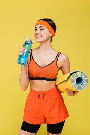 happy sportswoman with fitness mat drinking water from sports bottle isolated on yellow