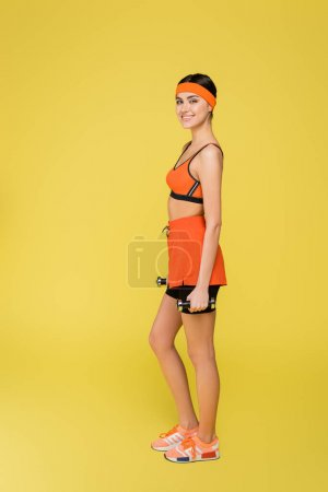 Foto de Full length view of young sportive woman standing with dumbbells isolated on yellow - Imagen libre de derechos