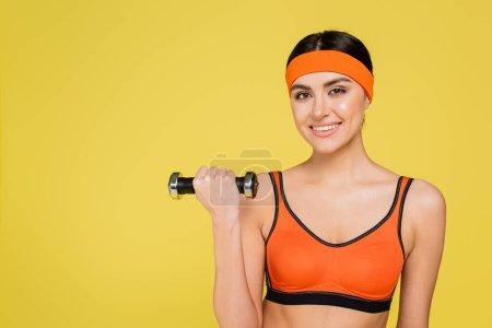 Photo pour Jolie sportive souriant à la caméra pendant l'entraînement avec haltère isolé sur jaune - image libre de droit