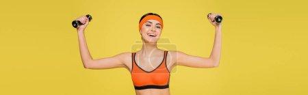 femme gaie en soutien-gorge de sport orange travaillant avec des haltères isolés sur jaune, bannière