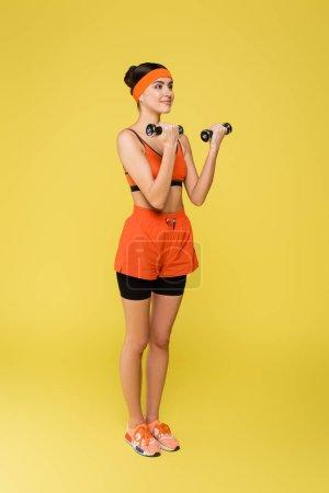 Ganzkörperansicht der sportlichen Frau in orangefarbener Sportbekleidung beim Training mit auf gelb isolierten Kurzhanteln