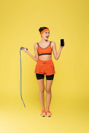 Photo pour Vue pleine longueur de la sportive avec corde à sauter tenant smartphone avec écran vide isolé sur jaune - image libre de droit
