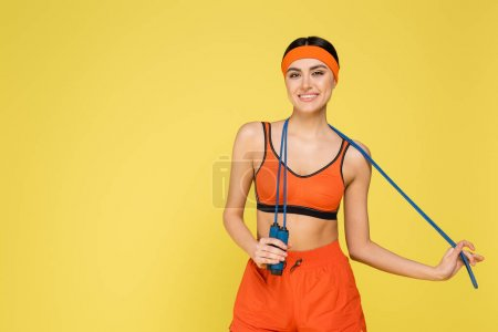 Foto de Pretty sportswoman with skipping rope smiling at camera isolated on yellow - Imagen libre de derechos