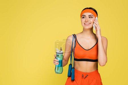 Photo pour Femme souriante avec bouteille de sport et corde à sauter appelant sur smartphone isolé sur jaune - image libre de droit