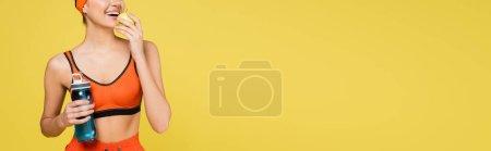 Photo pour Vue recadrée de la femme avec bouteille de sport manger pomme fraîche isolé sur jaune, bannière - image libre de droit