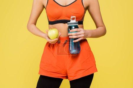 Photo pour Vue recadrée d'une sportive tenant une pomme verte et une bouteille de sport isolées sur jaune - image libre de droit