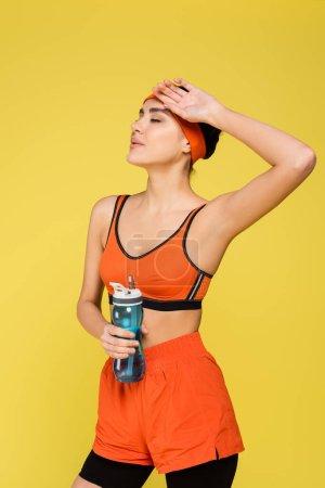 Photo pour Femme fatiguée avec bouteille de sport tenant la main près du visage isolé sur jaune - image libre de droit