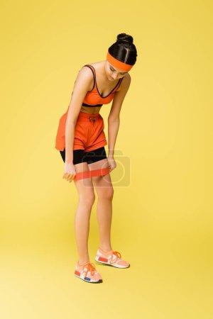 Foto de Sportive woman putting resistance band on legs on yellow background - Imagen libre de derechos