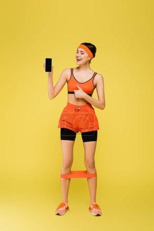 Photo pour Sportive heureuse avec téléphone portable montrant pouce vers le haut isolé sur jaune - image libre de droit