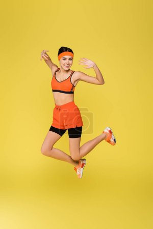 Photo pour Excitée sportive souriant à la caméra tout en sautant isolé sur jaune - image libre de droit
