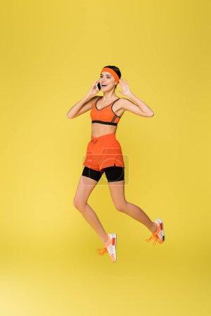 Photo pour Excitée sportive parler sur téléphone portable tout en sautant isolé sur jaune - image libre de droit