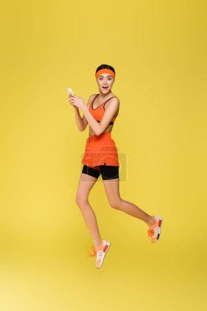 Photo pour Jeune sportive sautant tout en utilisant smartphone isolé sur jaune - image libre de droit