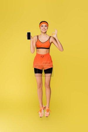 Photo pour Sportive joyeuse montrant geste correct et smartphone avec écran vide isolé sur jaune - image libre de droit