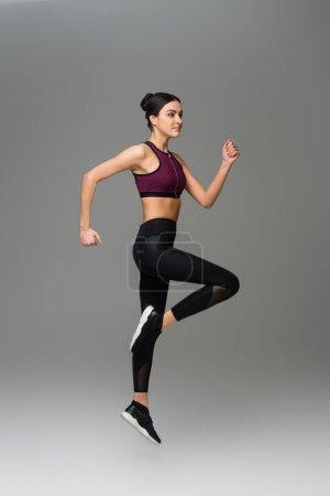 Photo pour Vue pleine longueur de la femme sportive sautant sur fond gris - image libre de droit