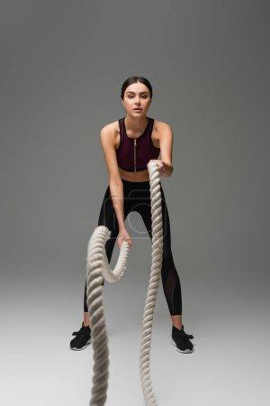 Photo pour Vue pleine longueur de la femme sportive travaillant avec des cordes de combat sur fond gris - image libre de droit