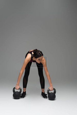 woman in black sportswear working out with kettlebells on grey background