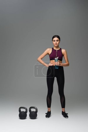 confident woman with sports bottle standing near kettlebells on grey background