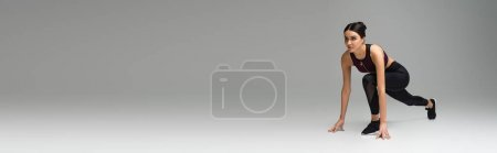 Foto de Sportswoman in low start position on grey background, banner - Imagen libre de derechos
