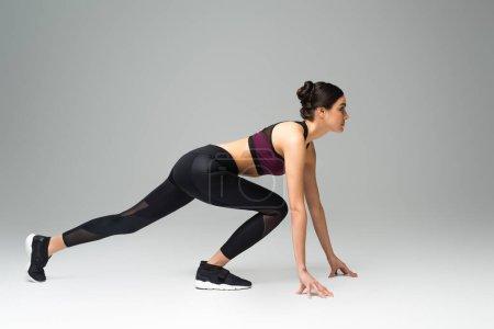 Foto de Side view of woman wearing black sportswear in low start position on grey background - Imagen libre de derechos
