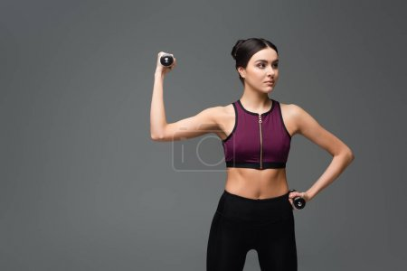 pretty sportive woman looking away while exercising with dumbbells isolated on grey