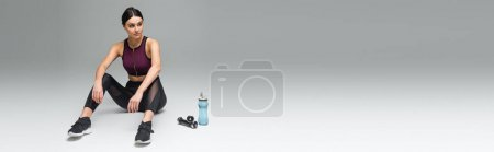 Photo pour Femme sportive regardant loin tout en étant assis près de la bouteille de sport et des haltères sur fond gris, bannière - image libre de droit