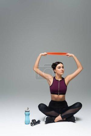Photo pour Femme en tenue de sport noire s'entraînant avec des élastiques tout en étant assise avec des jambes croisées sur fond gris - image libre de droit
