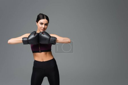 young sportswoman in boxing gloves looking at camera isolated on grey