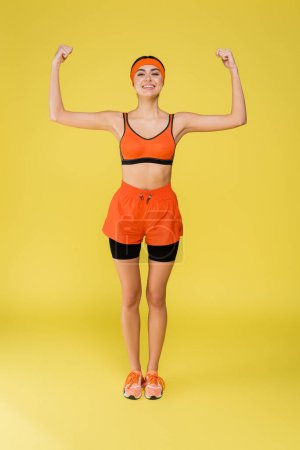 full length view of happy woman in orange sportswear showing muscles isolated on yellow
