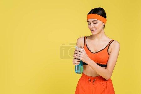 Photo pour Femme heureuse en orange sport ouverture bouteille de sport isolé sur jaune - image libre de droit