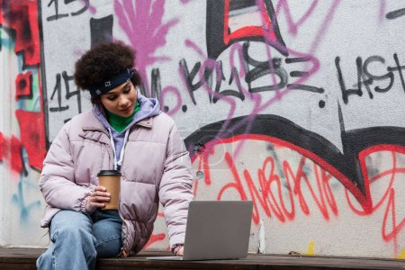 African american woman holding coffee to go and using laptop near graffiti outdoors