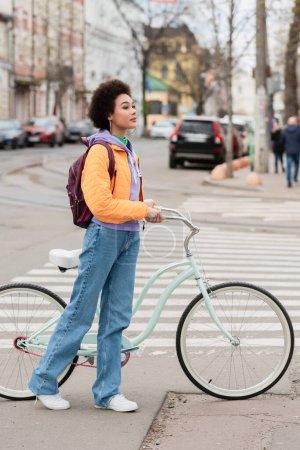 Junge Afroamerikanerin steht neben Fahrrad und Zebrastreifen im Freien