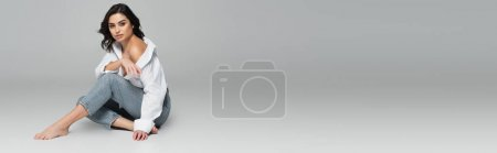 Photo for Sexy woman in jeans sitting on grey background, banner - Royalty Free Image