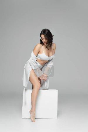 Photo pour Femme incroyable en sous-vêtements et robe de soie tenant sac à provisions sur fond gris - image libre de droit