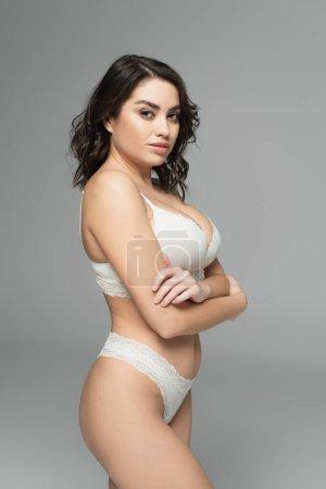 Photo pour Femme sensuelle en lingerie regardant la caméra isolée sur gris - image libre de droit