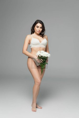 Photo for Pretty brunette woman in lace lingerie holding flowers and looking at camera on grey background - Royalty Free Image