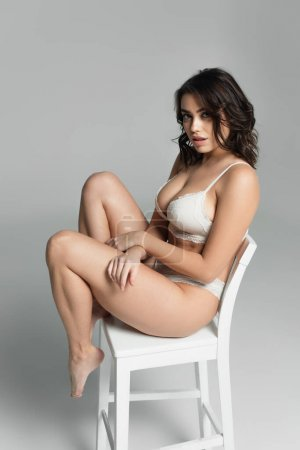 Young seductive woman looking at camera on white chair on grey background